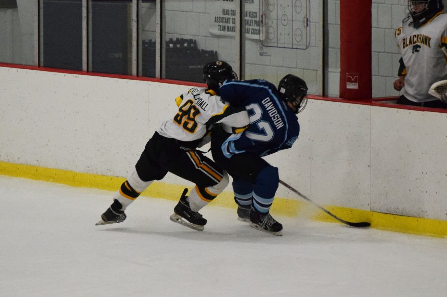 Junior Jimmy Kelly slams a player from Central Valley in the fight for the puck during the game on Oct. 27. Kelly is one of three players from Freedom who currently play on Blackhawk's hockey team through a cooperative agreement.