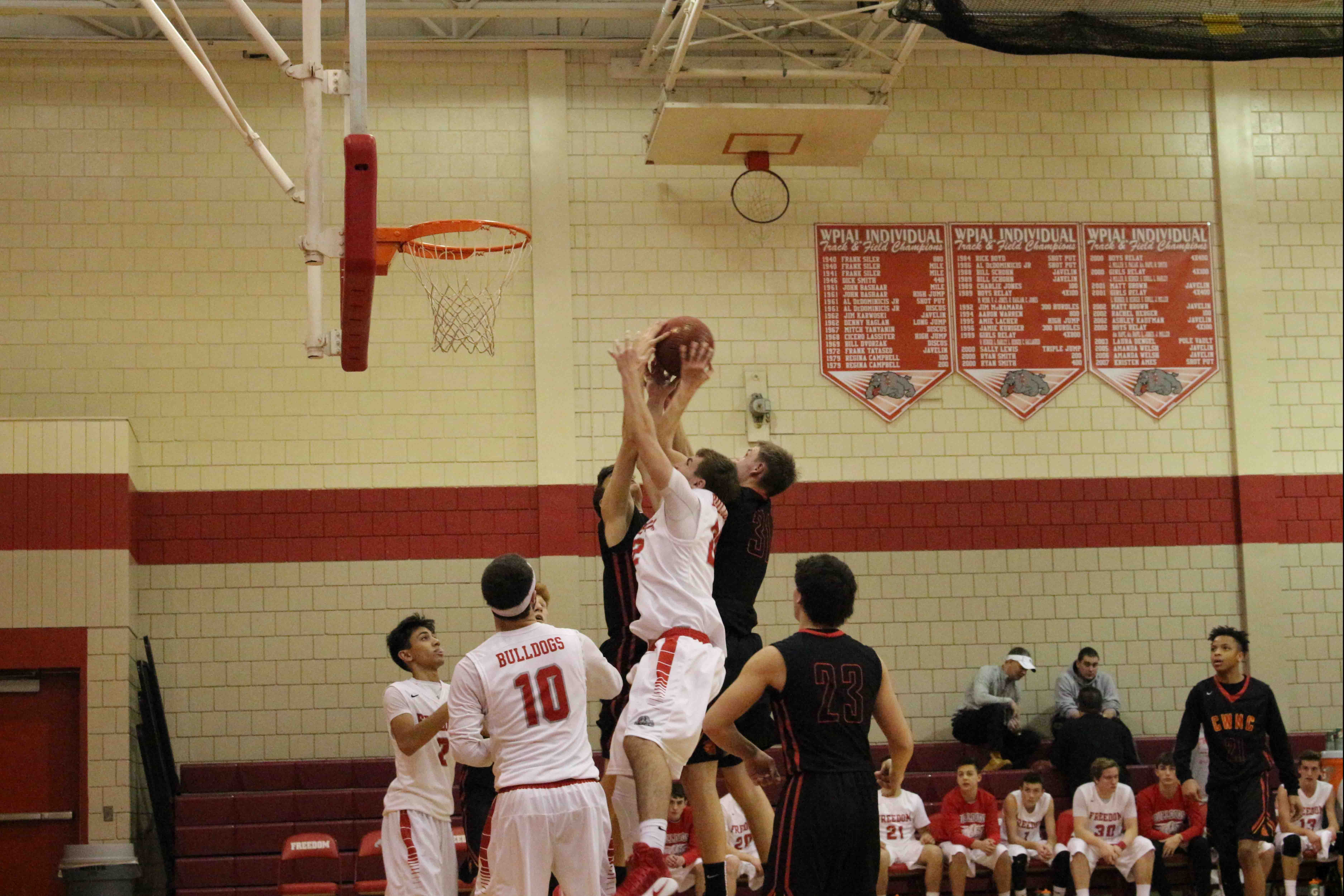 Senior Scotty Lazarus goes for a rebound against two of North Catholic's players.