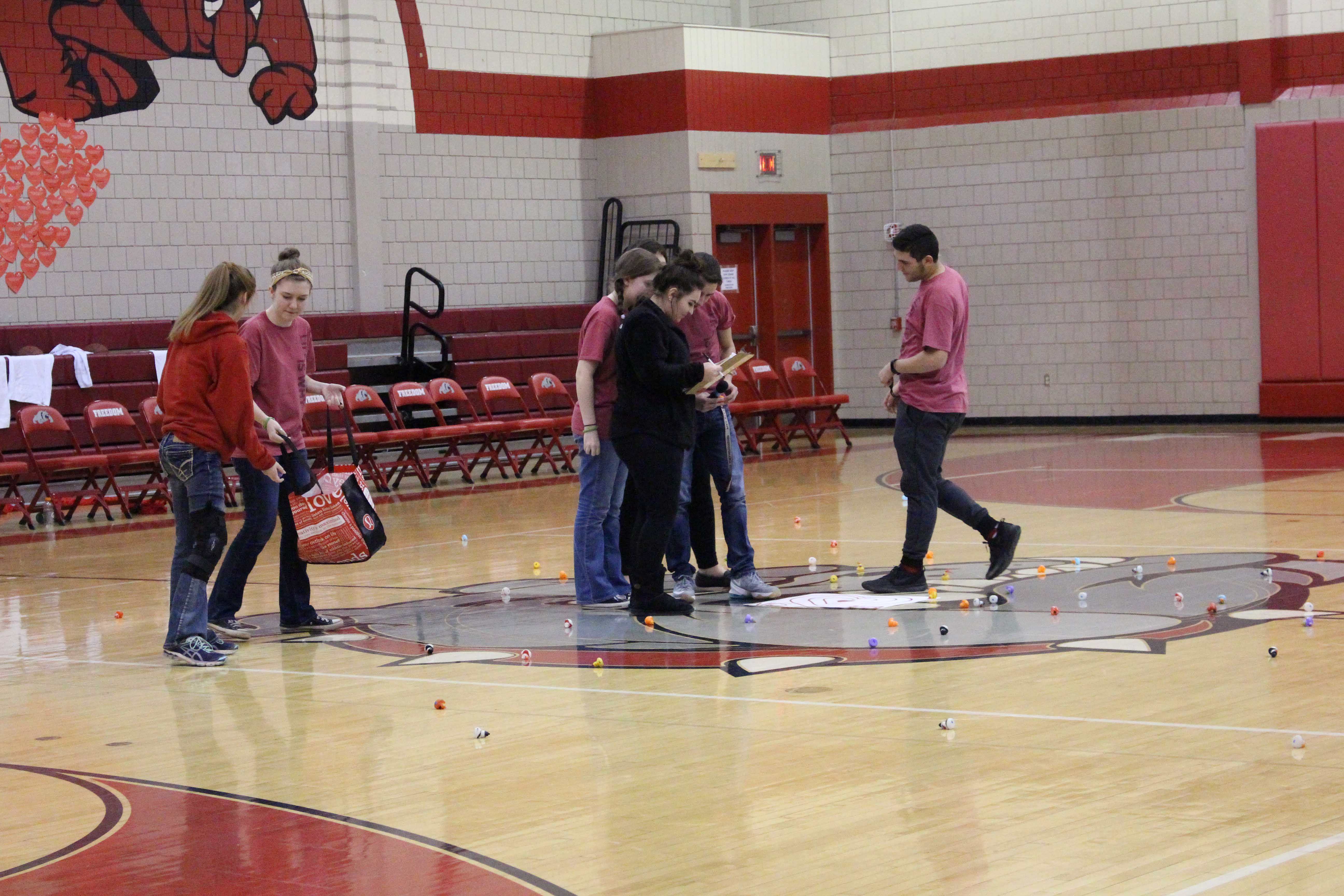 """NHS members collect the ducks scattered across the court after the """"chuck-a-duck"""" contest."""