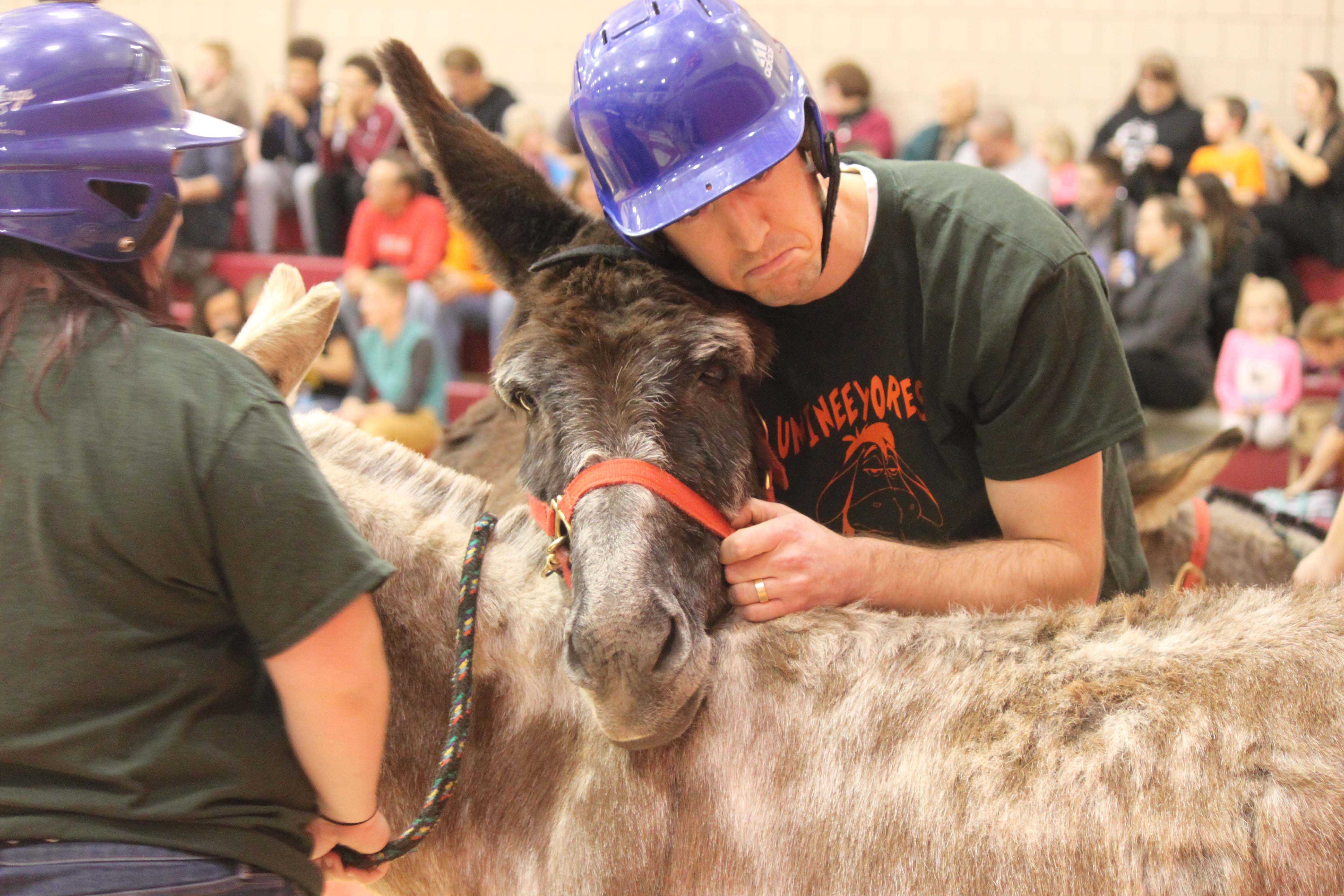 High school teacher Nate Langelli consoles his donkey after its resistance to play the game on Feb. 27 in the high school gymnasium.