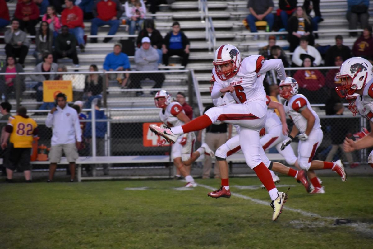 Senior Carson Gilarno kicks off for Freedom against New Brighton during the game on Sept. 8.