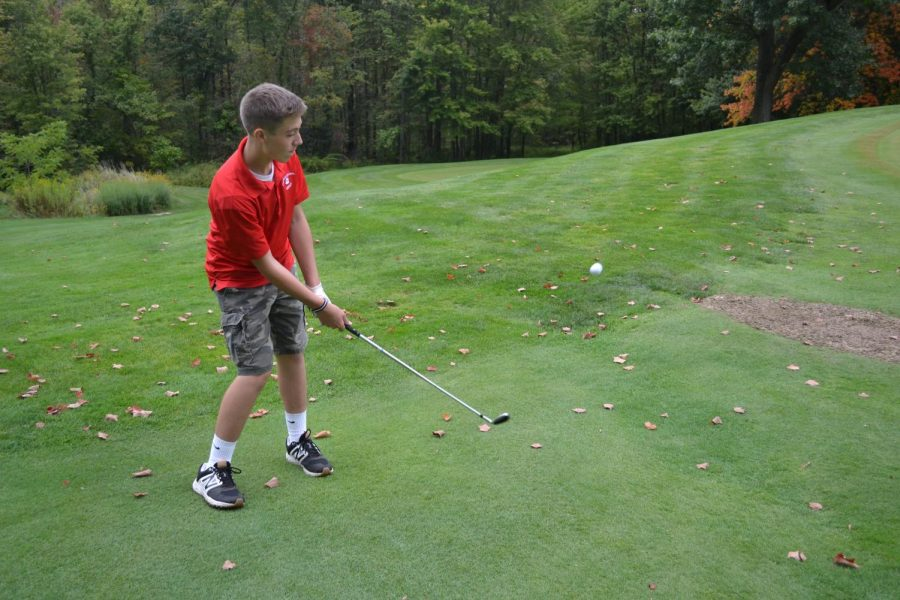 Sophomore Nolan Colaric Chips his Golf Ball towards the hole.