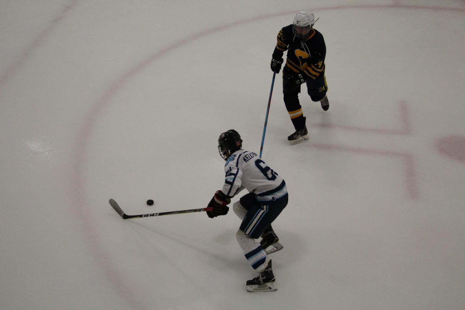 Senior Jimmy Kelly-Tindall skates around a defender with the puck in a game against Carrick.