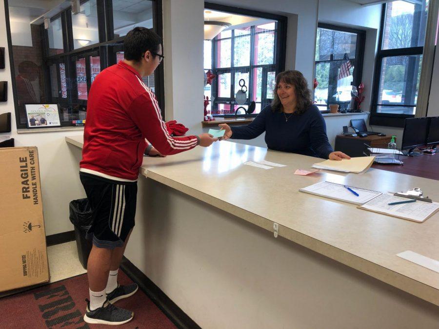 Sophomore Brandon Majors hands secretary Mucho absent excuse.