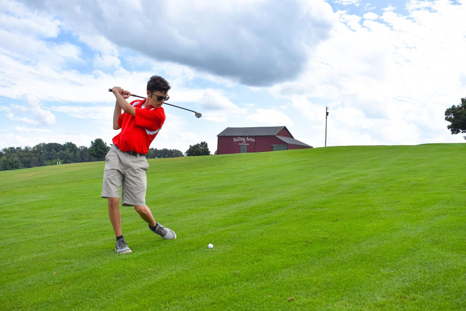 Sophomore Kameron Skrobacz pulls back his Four Hybrid to hit the ball on the North Course at Rolling Acres.