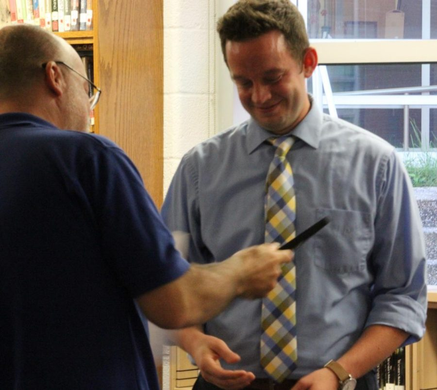 Teacher Aaron Fitzpatrick is handed his certificate for 2018 PSPA Journalism Teacher of the Year by PSPA Board President Paul Fantaski in the Middle School library during the Sept. 18 school board meeting.