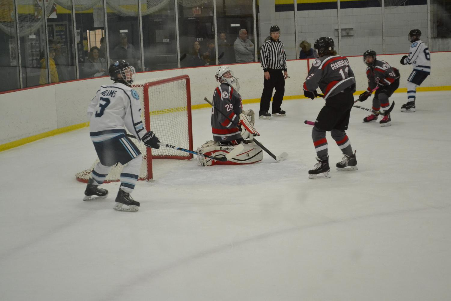 Senior Riley Adams (left) is shown waiting by the net for the puck in the hopes of scoring at the game on Oct. 18