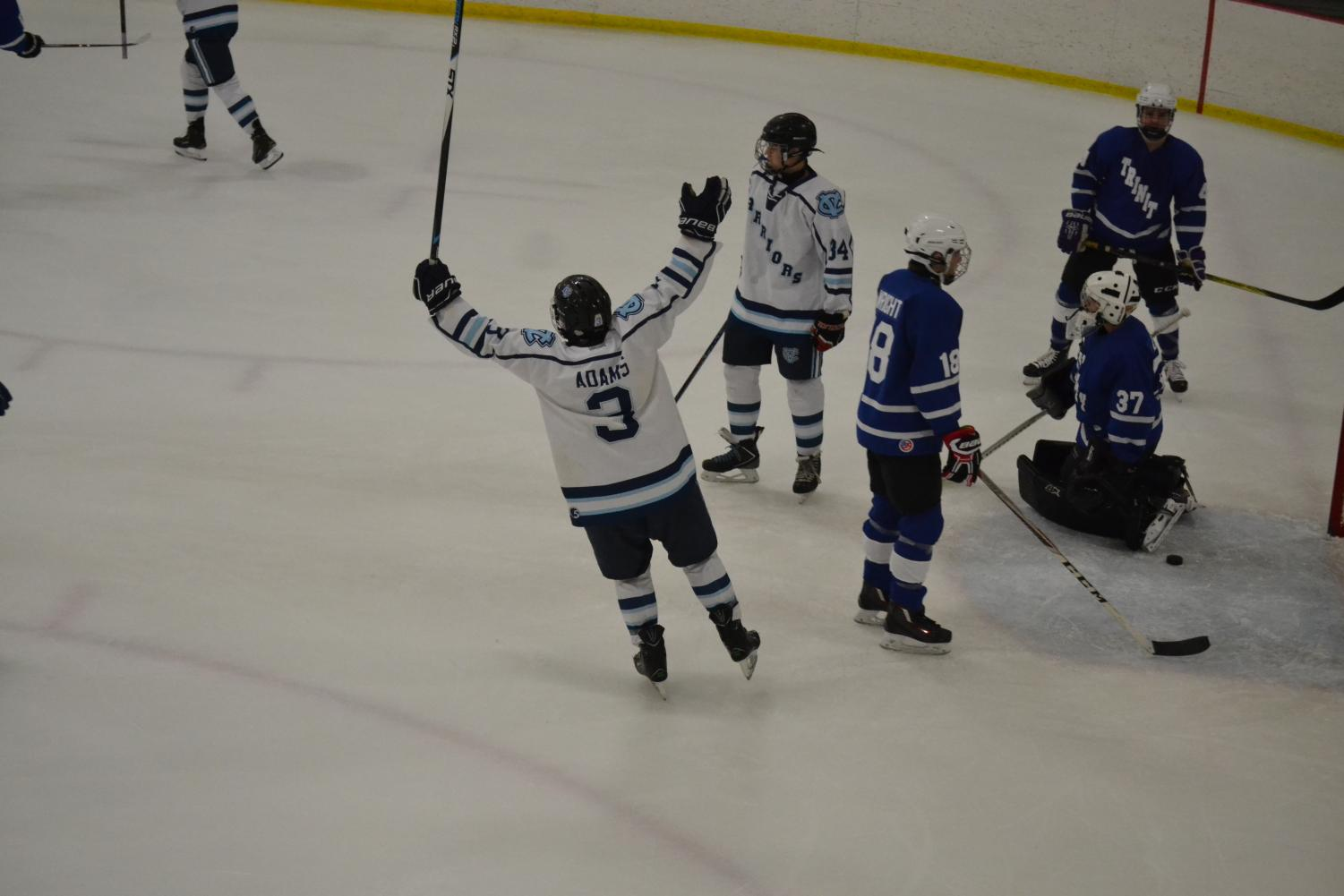 Senior Riley Adams celebrates with his arms in the air after he assists on a goal.