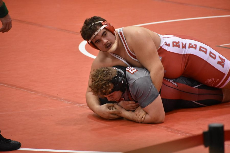 Looking to Coach Jim Covert, junior Fernando Franco seeks advice on how to earn more points during his match on Jan. 5 during the MAC tournament.