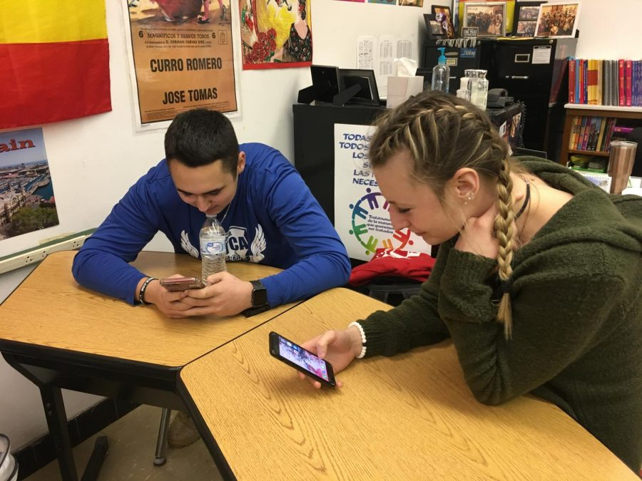 Juniors+Morgan+Swab+and+Brandon+Majors+use+their+phones+as+a+source+of+communication+on+February+19+at+the+end+of+their+Spanish+3+class.