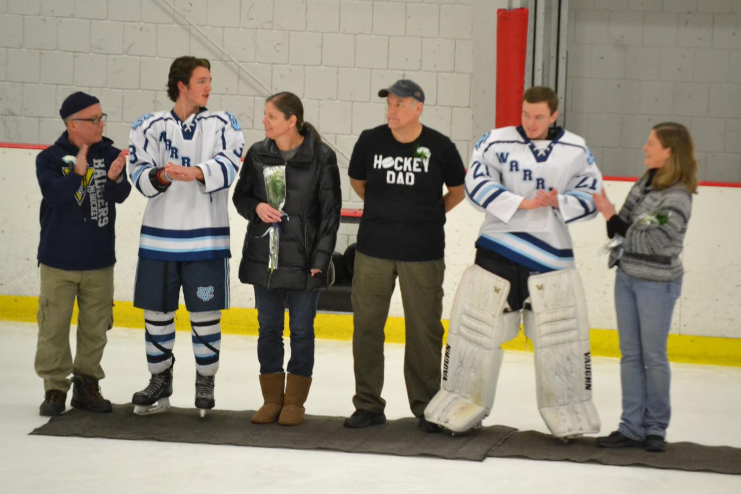 Seniors Riley Adams and Sam Romutis stand in the middle of their parents, respectively, for their commitment as seniors to the hockey team at Senior Night on Feb. 14