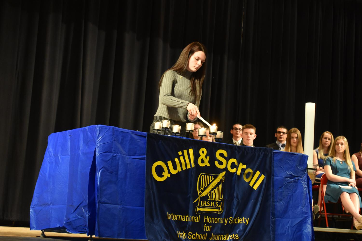 Lighting the candle of judgement, senior Claudia Huggins one of the six returning members starts off the induction ceremony.