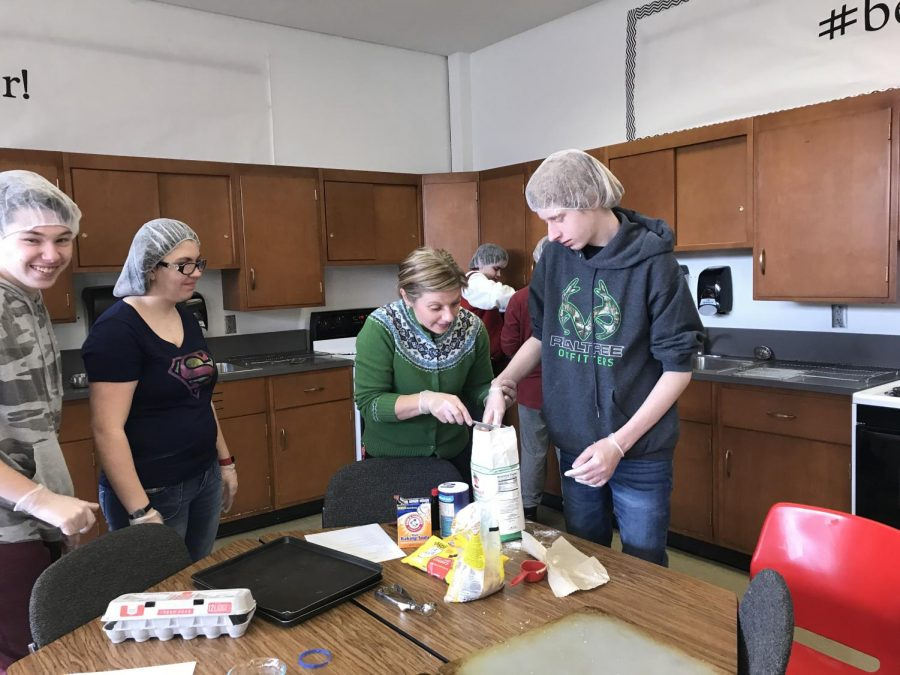 April+English+assists+freshman+John+Nelson+with+measuring+flour+as+sophomore+Micha%0AHenley+works+with+another+student+behind+them+to+make+pastries+for+Cafe+116.