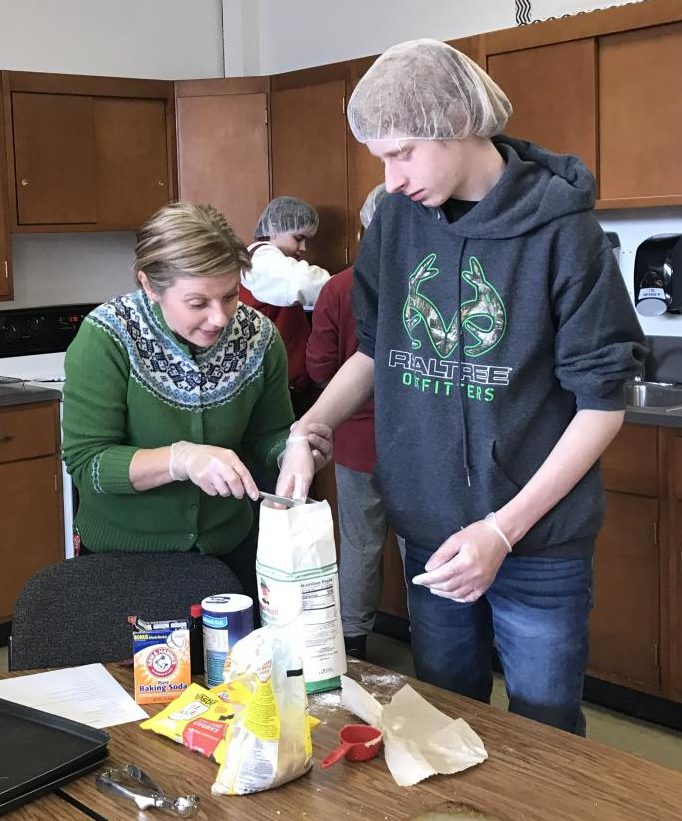 April English assists freshman John Nelson with measuring flour as sophomore Micha Henley works with another student behind them to make pastries for Cafe 116.
