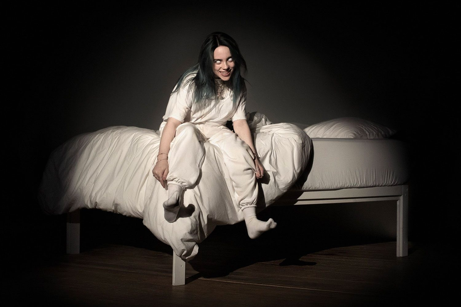 "Eilish sits on a bed with light focused on her as her album cover for ""When We All Fall Asleep Where Do We Go?"""