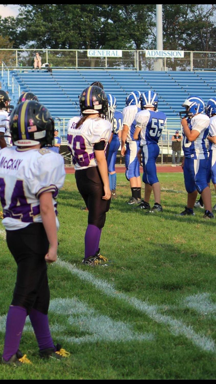 Senior Tabitha Scimio (number 58) takes the field with the rest of her football team before a game when she was in middle school.