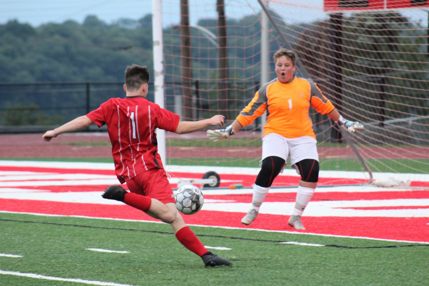 Senior Thomas Young gets ready to strike the ball to the left conner for another Freedom goal as Carlyton's goalie charges out towards him.