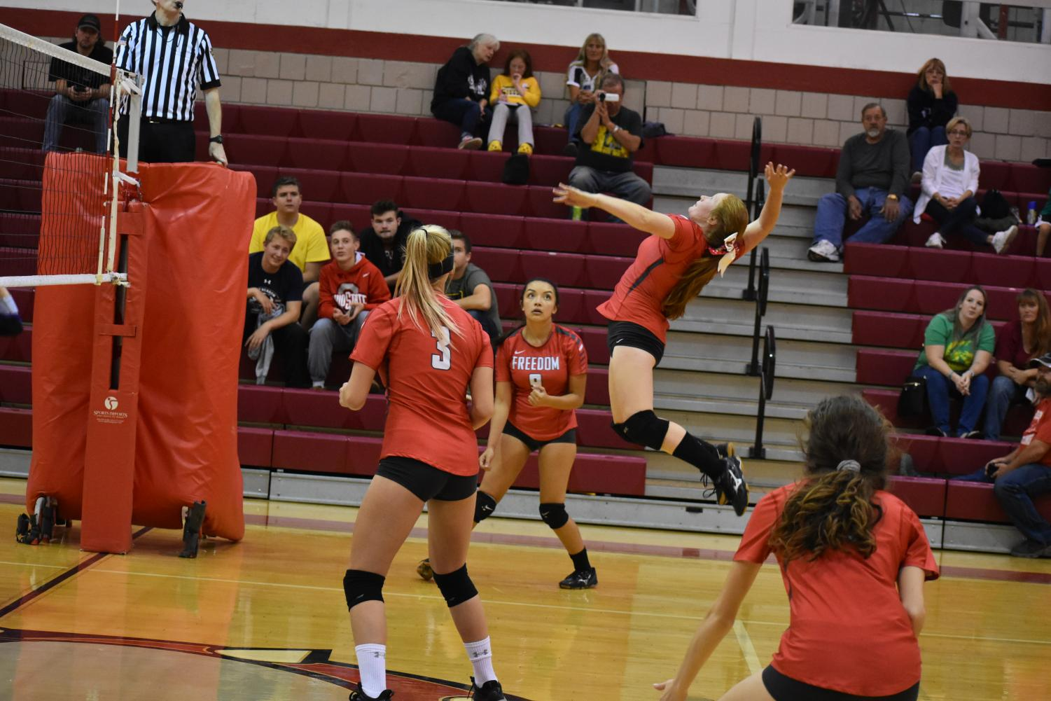 Junior Alexis Surenda jumps to hit the ball in an attempt to launch it over to the other side of the third hit against OLSH on Oct. 10.