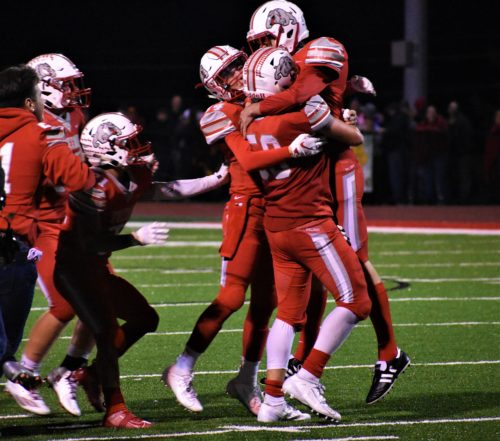 Teammates hug and lift Garrett Paxton moments after he made the game-winning field goal to keep the team's undefeated season alive and defeat their rival New Brighton.