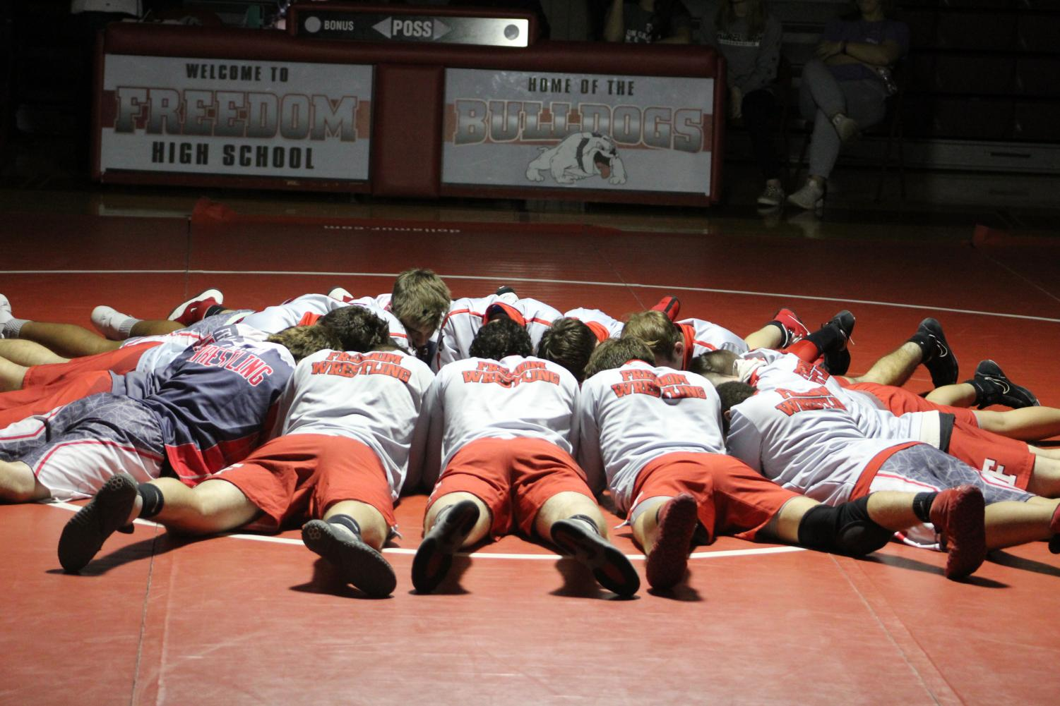 The wrestlers circle up in the middle of the matt to get themselves ready before their match on Dec. 13.