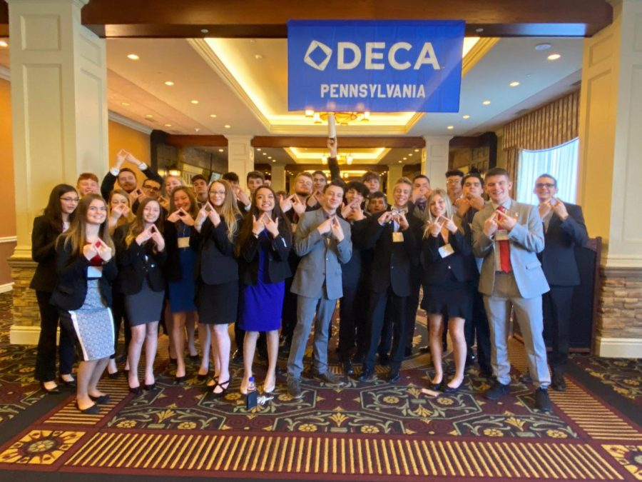Deca+members+stand+inside+Hershey+Lodges+lobby+and+pose+for+a+photo.