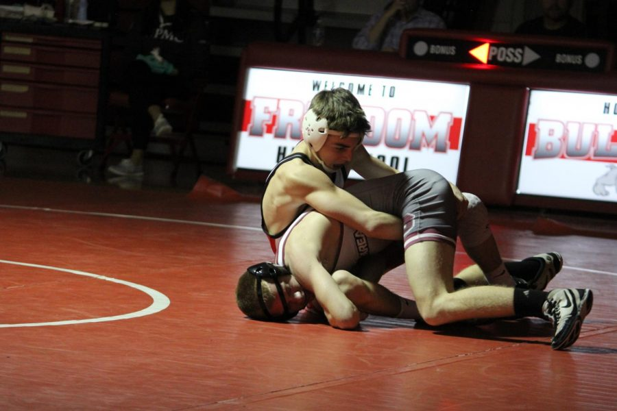 At a home match against Beaver on Jan. 15, freshmen Matthew Schultheis attempts to pin his opponent down while they try to escape the hold.