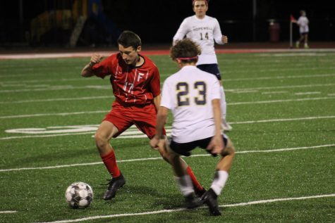 Junior Joseph Hartle takes on a Hopewell Viking defender to advance the ball up the field on Oct. 12.