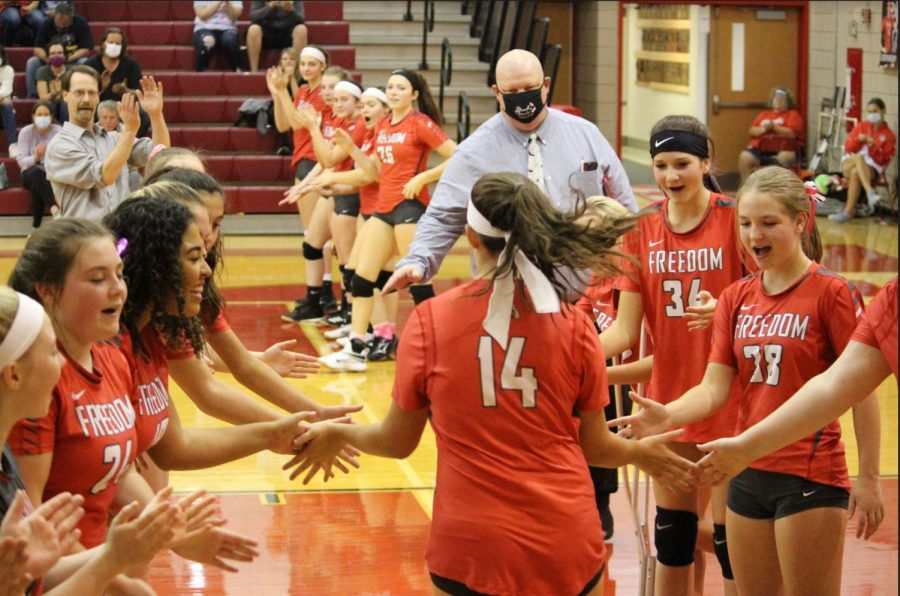 Junior Olivia Evans gives her teammates high fives as she prepares herself for the last game of the season against New Brighton.
