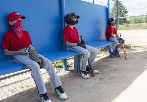 Youth baseball players, some with masks on, sit far apart as they wait for their turn to step into the batter's box.