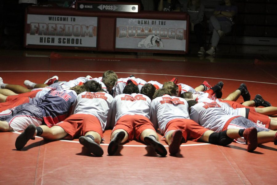 The wrestling team huddles together on the mat for a pep talk as they prepare for their matches.