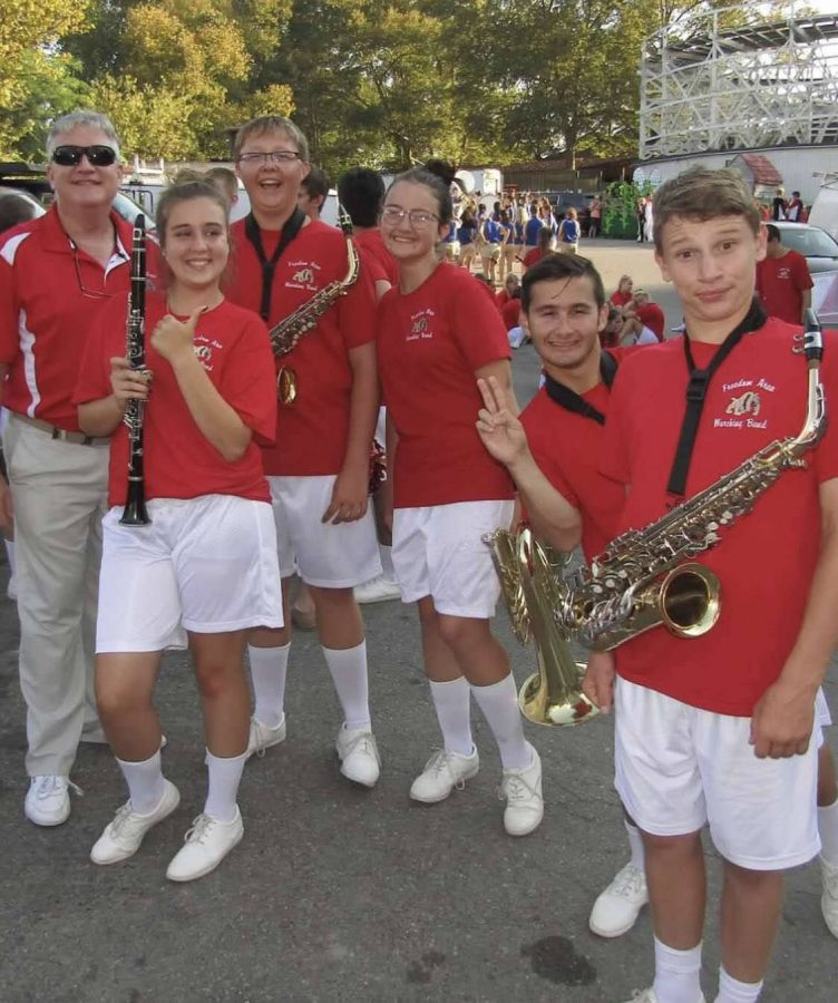 Band director Robert James poses with students before marching at the Kennywood parade in Aug. of 2019.