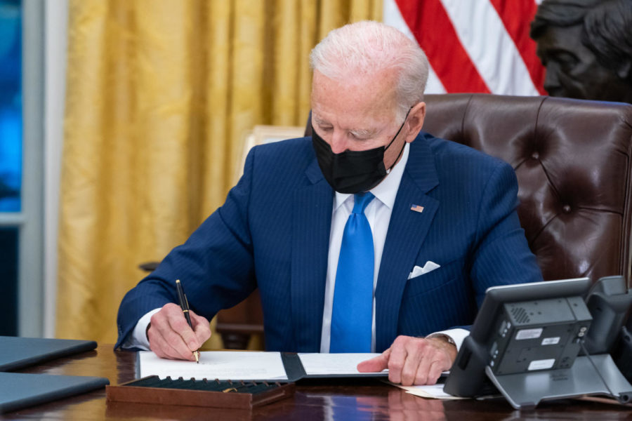 President Joe Biden signs executive orders on immigration Tuesday, Feb. 2, 2021, in the Oval Office of the White House.