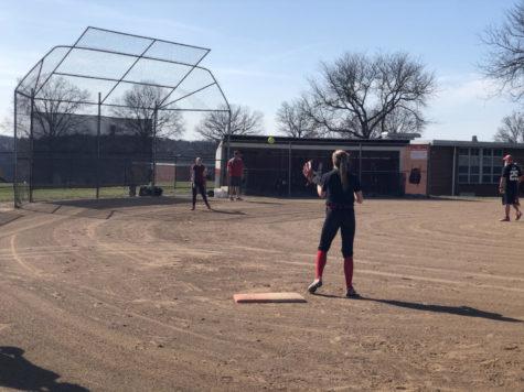 Senior Erica Gazdik makes a throw to freshman Shaye Bailey at first base during a practice on March 22.