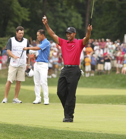Celebrating sinking his 18th hole shot, Tiger Woods puts his hands and club in the air at the AT&T National Tournament.