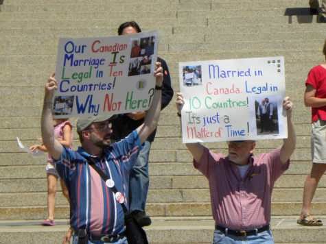Activists stand outside a government house in Minnesota during a rally for LGBTQ+ rights, including same-sex marriage.