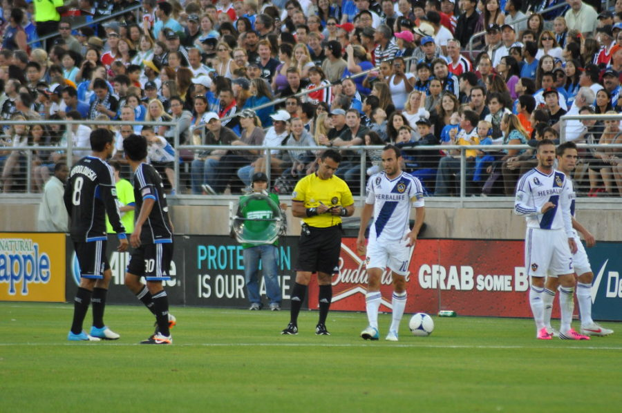 After calling a foul and giving a yellow card, the referee writes down the name of the guilty Los Angeles Galaxy player.