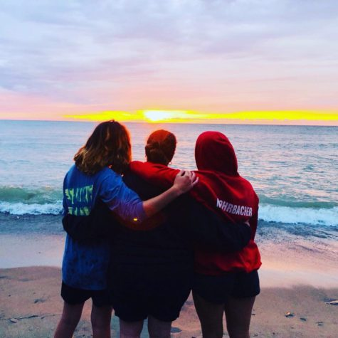 Sophomore Julia (left) and junior Renae Mohrbacher (right) enjoy a sunset on Lake Erie with their mother, Kristie (center), in August of 2019.