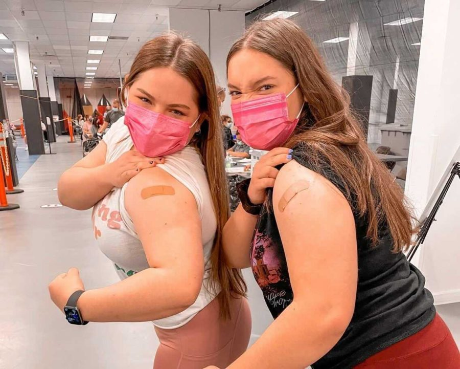 Juniors Alexis Rinere and Emily Frashure show off their arms after receiving the Pfizer-BioNTech vaccine on April 19.